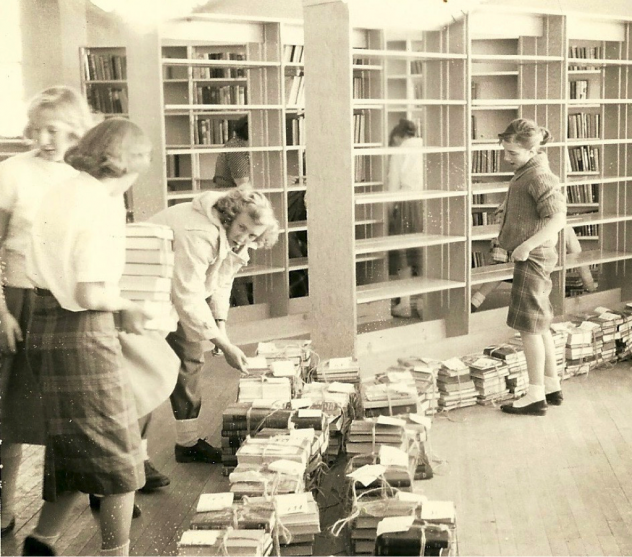 Women organizing books on floor next to empty shelves