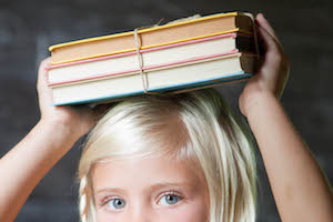 Child carrying three books on her head