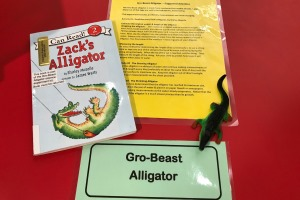 book, yellow instruction sheet, and alligator toy on a table